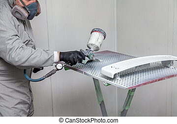 A male worker paints with a spray gun a part of the car body in silver after being damaged at an accident. Plastic elements from the vehicle during the repair in the workshop auto service.