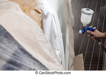 A male worker paints with a spray gun a part of the car body in white after being damaged at an accident. Door from the vehicle during the repair in the workshop. Auto service industry professions