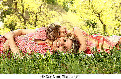 Mama and her little daughter lie on the grass - a Mama and ...