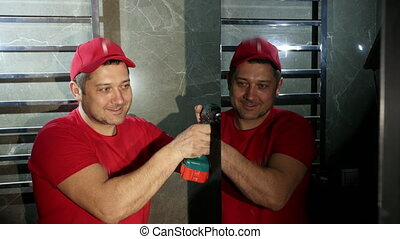 a man, a Builder, in a red cap and t-shirt, uses a cordless screwdriver