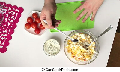 A man adds salt to a container with salad. Cooking salad of crab sticks, cheese, eggs and tomatoes.