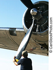 airplane propeller - A man adjusts a large airplane...