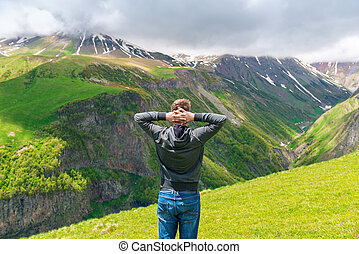 A man admires the beautiful scenery in the mountains, the view from the back