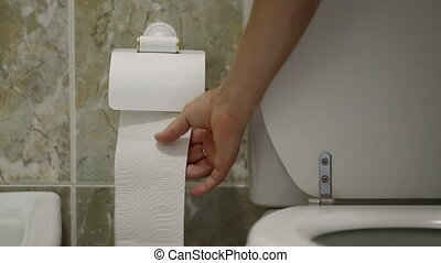 A man after constipation, pulls toilet paper. - A man after...