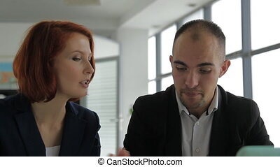 a man aged businessman business consultant talking with his client, a woman in a large, bright office.