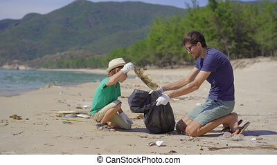A man and a boy in gloves collect plastic trash on a beach. The problem of garbage on the beach sand caused by man-made pollution. Eco campaigns to clean the environment. Ecological volunteering concept. Teaching children to care about nature.