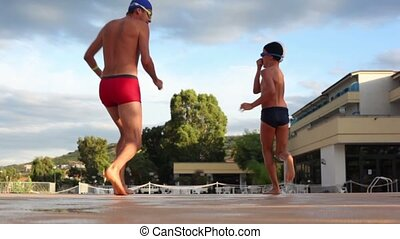 A man and a boy running and jumping into the pool
