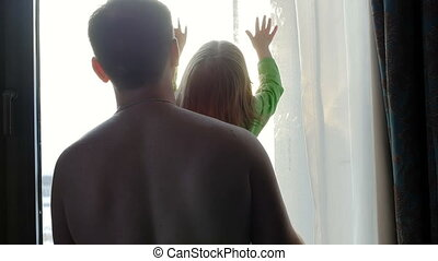 A man and a child are looking out the window and playing with the rays of the sun, knocking on the window. Family.