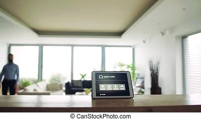 A man and a tablet with smart home screen. - A handsome man...