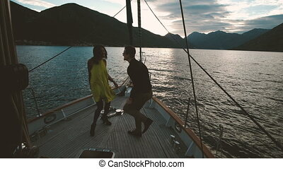 A man and a woman are dancing at the stern of the yacht at sunset.