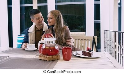 a man and a woman are sitting in the restaurant of love