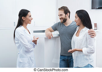 A man and a woman came to see a dentist. The receptionist fills in the form and interviews the patients.