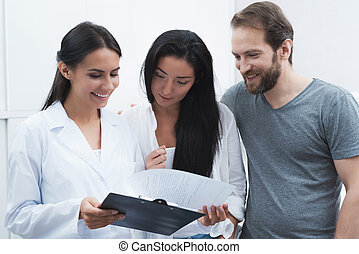A man and a woman came to see a dentist. They were met by the receptionist, he shows them the information on the form.