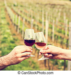 A man and a woman check with glasses of wine. Glasses with red wine in the female and male hands. wine tasting, vineyards.