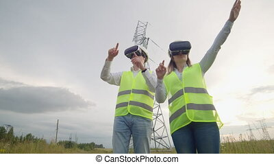 A man and a woman engineer in VR glasses control the power...