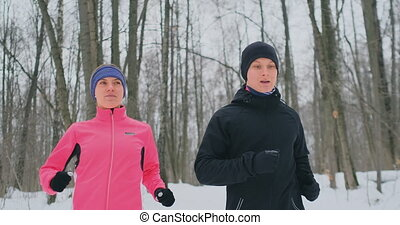 A man and a woman in a pink jacket in the winter running through the Park in slow motion. Healthy lifestyle