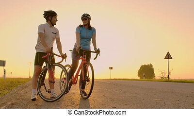 A man and a woman in helmets with bicycles stand and talk at...