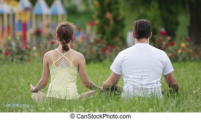 A man and a woman meditate in bliss. Young yoga instructors practice in a city park on green grass. Look from behind.