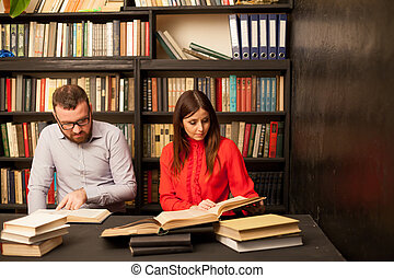 a man and a woman read books in the library are preparing for the exam 1