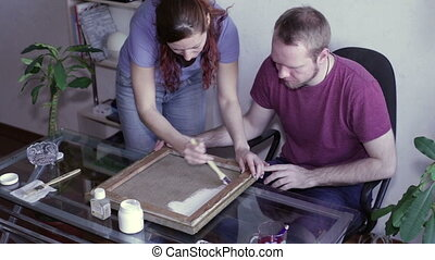 A man and a woman restore canvas - A woman is standig at a...