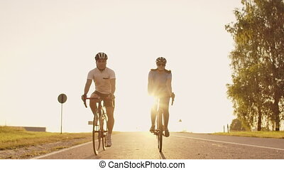 A man and a woman ride sports bikes on the highway at sunset...