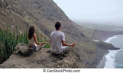 A man and a woman sitting on top of a mountain looking at the ocean sitting on a stone meditating in a Lotus position. The view from the back. Canary islands