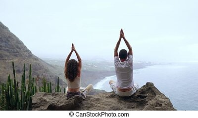 A man and a woman sitting on top of a mountain looking at the ocean sitting on a stone meditating raising their hands up and performing a relaxing breath. Canary islands