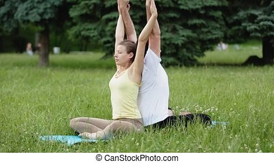 A man and a woman stretching before doing exercises. Young yoga instructors practice in a city park on green grass. Successful young people perform acro yoga exercises.