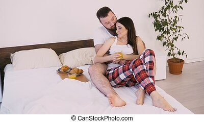 a man and a woman wake up in the morning, breakfast in bed