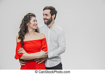 A man and a woman with long hair, supporting each other with love. Valentine's Day. A woman dressed in a red dress of a man in a white shirt.