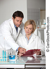 A man and a woman working in a lab.