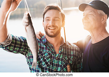 A man and an old man are posing with a fish caught by a man against a river in which the sun is reflected
