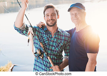 A man and an old man are posing with a fish that a man caught. Behind them, the sun is reflected in the river