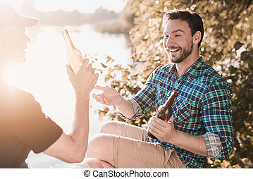 A man and an old man are sitting with a beer on the river bank and having fun.