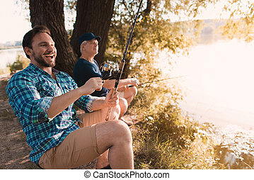 A man and an old man on the river bank. The man laughs and prepares to pull out the fish, the old man quietly fishes