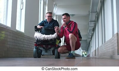 A man and his disabled wife are talking in the hallway.