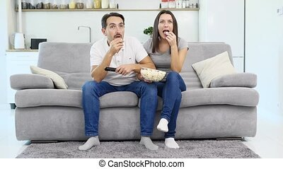A man and his wife watch TV