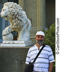 A man and the sculpture marble lion - A man with a beard in...