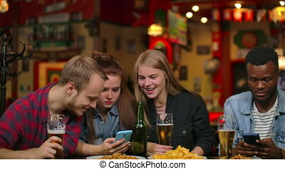 A man and two girls are sitting in a bar and looking at the...
