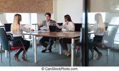 A man and two girls working in the office