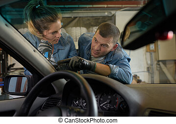 a man and woman changing windshield