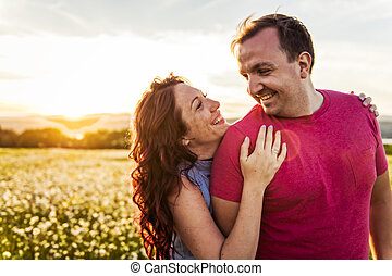 Man and woman on the daisy field at sunset
