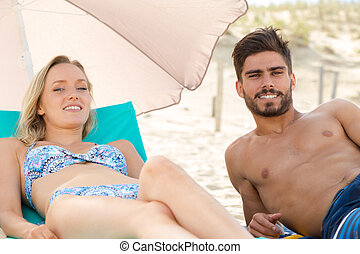 a man and woman sunbathing