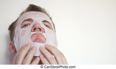 A man applies a moisturizing mask to his face.