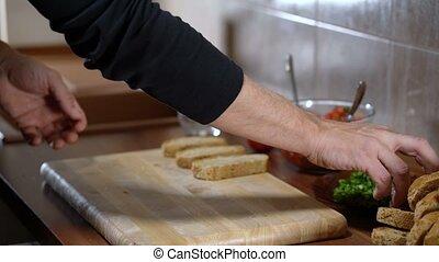 A man arranges bread for cooking bruschetta, close up
