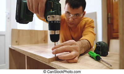 A man assembling furniture in the house