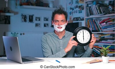 A man at the office table with foam on his face holds a watch in his hands