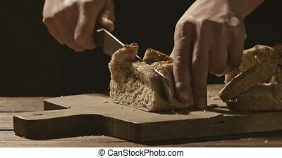 A man baker cuts a piece of white fresh bread on a wooden...