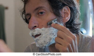 A man begins shaving his full beard with a safety razor