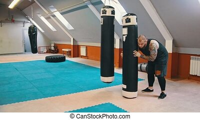 A man bodybuilder lift up and carrying the punching bag on the shoulder and squatting while the walking. Mid shot